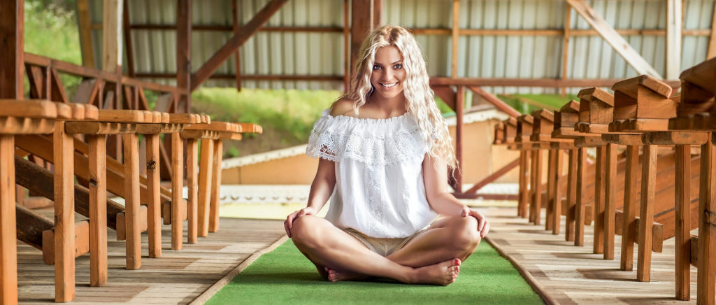 Girl model dressed in white dress sitting on synthetic grass among wooden chairs